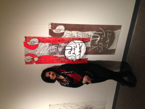 Poshya Kakil Ahmed stands next to her exhibit at the University
