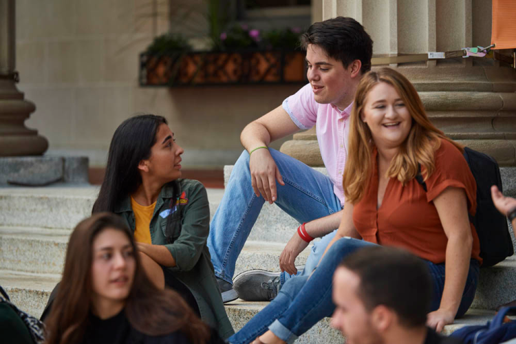 undergraduate students sit on LAC steps