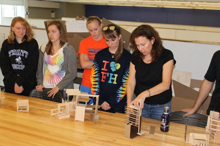 students and faculty work on architecture project at table